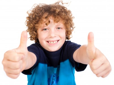 Smilling cute little boy gesturing thumbs up sign agaist white background.